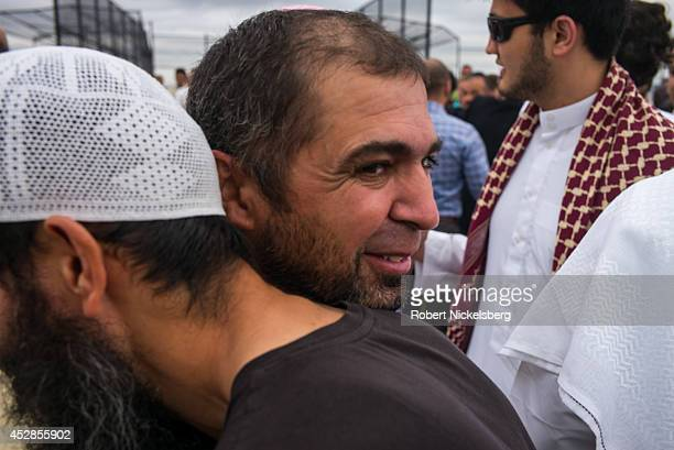 Muslim men greet each other during the traditional outdoor Eid alFitr celebrations July 28 2014 in the Brooklyn borough of New York The Eid holiday...