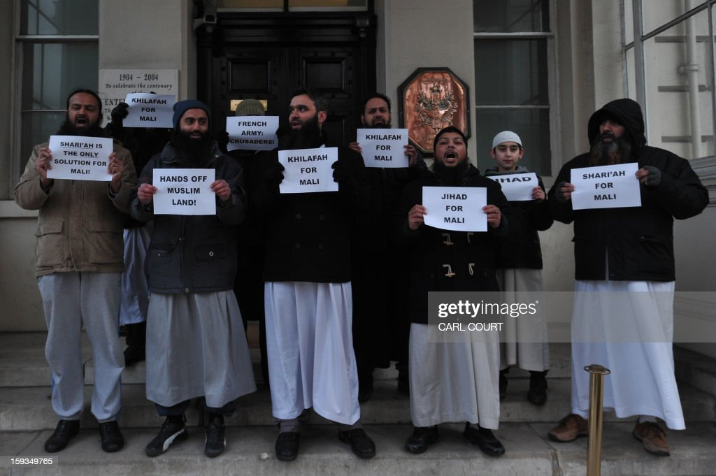 Muslim men hold up signs as they protest in response to French military action in Mali outside the French embassy in central London on January 12, 2013. Around 50 Muslim protesters shouted slogans and waved signs as they demonstrated outside the French embassy against French intervention in Mali. France sent troops on January 11 to help Malian forces hold back a rebel advance towards the capital Bamako, and on January 12 Paris announced that a French military pilot had been killed.