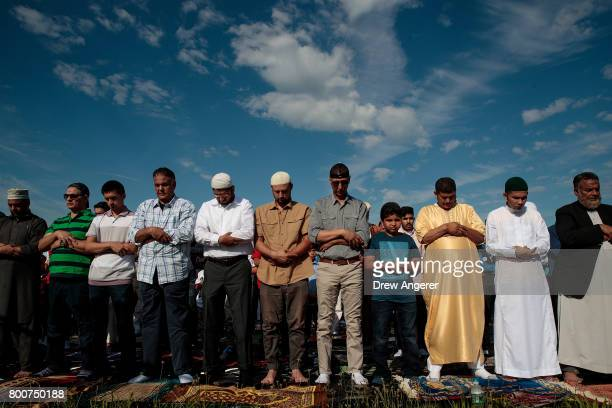 Muslim men participate in a group prayer service during Eid alFitr which marks the end of the Muslim holy month of Ramadan in Bensonhurst Park in the...