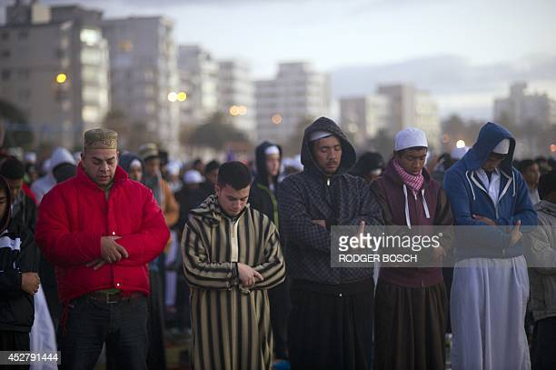 Muslim men pray at Seapoint Promenade a popular public area next to the sea before trying to sight the new moon which will signify the end of the...