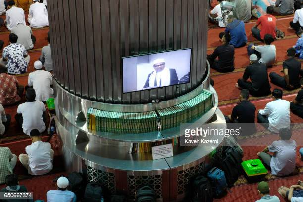 Muslim men sit listening to the Imam who appears on a TV screen in Istiqlal Mosque on a Friday on November 25 2016 in Jakarta Indonesia Istiqlal...