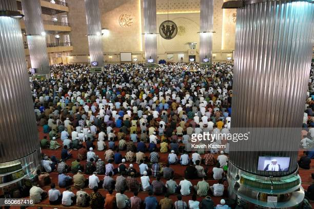 Muslim men sit listening to the Imam who appears on LCD Television screens in Istiqlal Mosque on a Friday on November 25 2016 in Jakarta Indonesia...