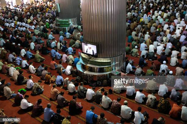 Muslim men sit listening to the Imam who appears on TV screens in Istiqlal Mosque on a Friday on November 25 2016 in Jakarta Indonesia Istiqlal...