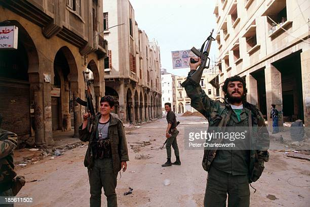 Muslim militia fighters belonging to the Amal Shi'ite faction with their AK47 semiautomatic rifles move to a position on the west side of the 'Green...