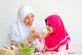 Muslim mother and her daughter are eating cookies together with a bowl of vegetable salad on white background.