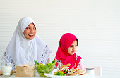 Muslim mother and her daughter are looking in the same direction with vegetable salad on the table and white background.