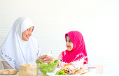 Muslim mother and little girl look to each other and smile also hold milk with bowl of vegetable salad on the table in front of white background.