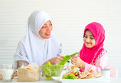 Muslim mother discuss and teach about vegetable for food to her little girl with white background.