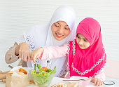 Muslim mother point to vegetable salad while little girl with pink hijab has fun with mixing salad put on the table