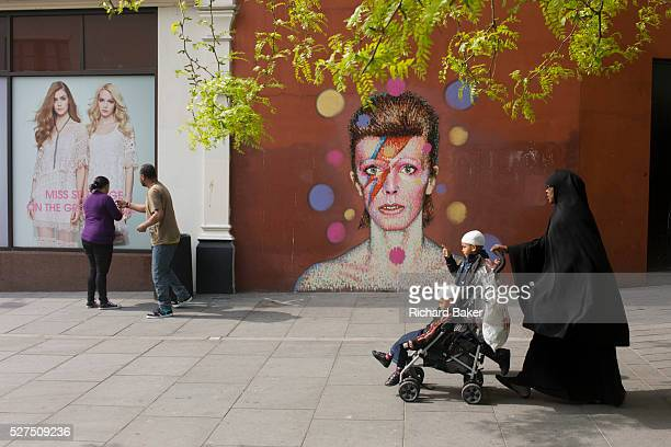 A Muslim mother with her children walks past the mural of iconic musician and singer David Bowie has appeared on the wall of Morleys department store...