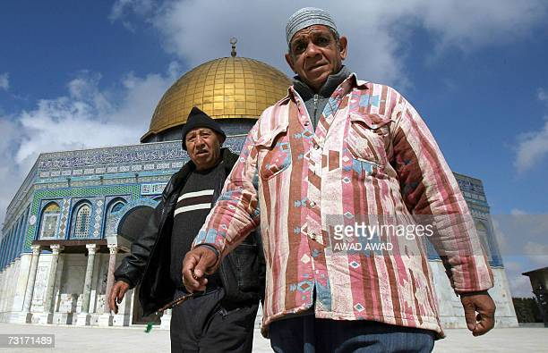Muslim Palestinian men walk past the Dome of the Rock as the new minbar or pulpit is put into place in the AlAqsa Mosque close by in annexed east...