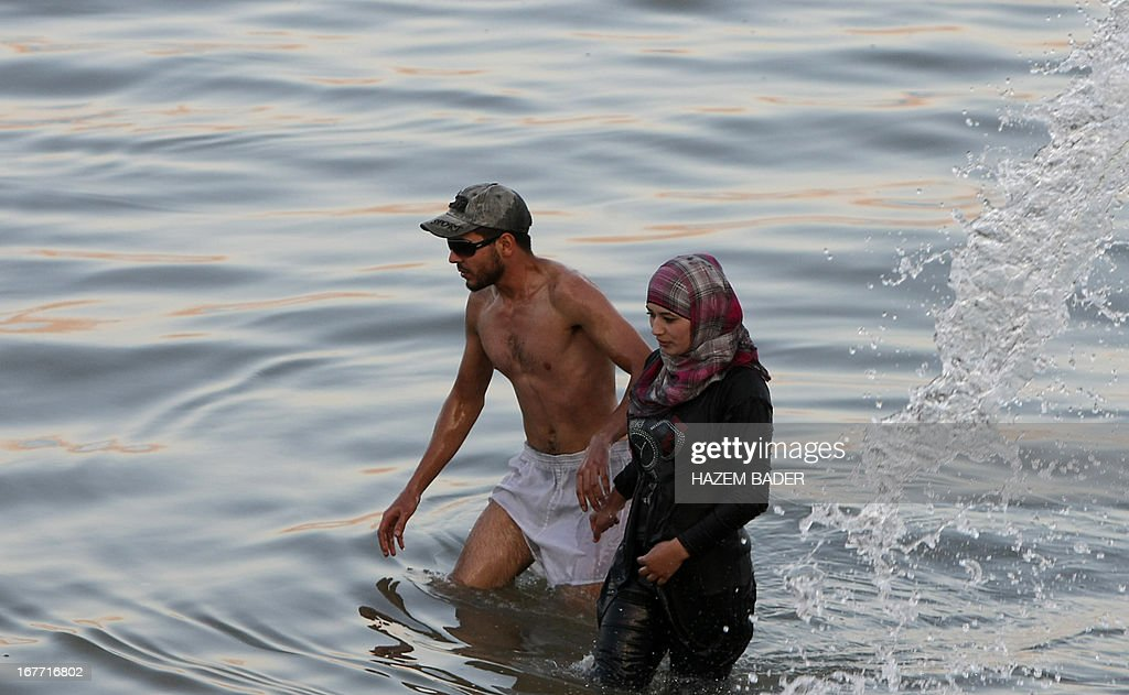A Muslim Palestinian woman and her husband leave the water at the Dead Sea at the Biankini beach located along the northern shore near the city of Jericho, in the Israeli occupied West Bank, on April 28, 2013. Palestinians can access this area of the Dead Sea without an Israeli government permit. AFP PHOTO/HAZEM BADER