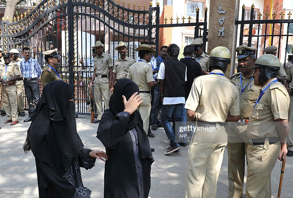 Muslim pedestrians walk past as Indian policemen stand guard at the main gate of The M. Chinnaswamy Stadium in Bangalore on December 25, 2012. Police were out in full force in the southern Indian city as part of a massive security operation ahead of Pakistan's first cricket tour of India for five years. AFP PHOTO/Manjunath KIRAN