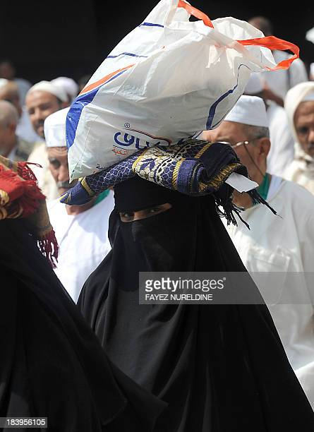 A muslim pilgrim carries a bag and a carpet on her head as she arrives to perform the afternoon prayer in Mecca's Grand Mosque on October 10 as more...