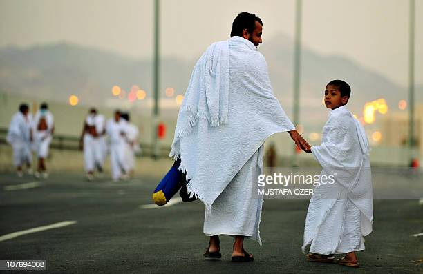 A Muslim pilgrim walks with his son along the road in the Mina valley five kilometres east of the Saudi Arabian holy city of Mecca on November 14 as...