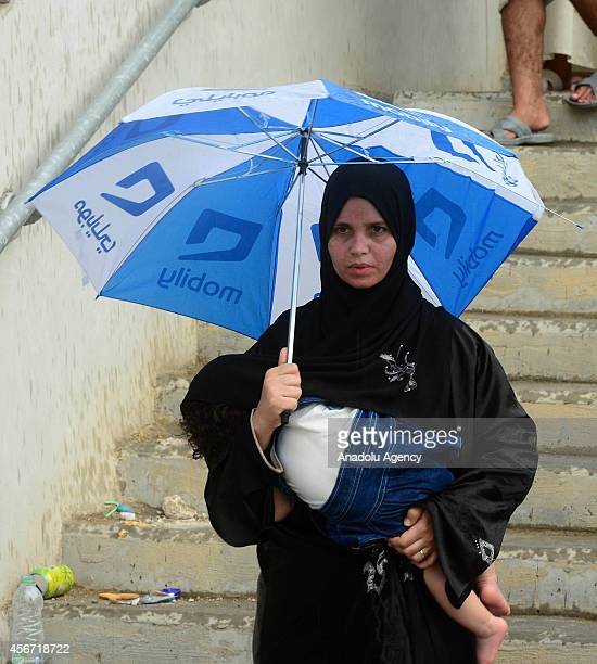 A muslim pilgrim with her son holds an umbrella in the mid afternoon during a rain in Mecca Saudi Arabia on October 5 2014