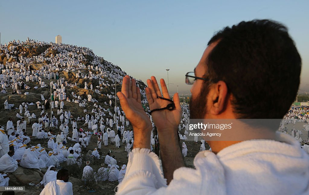 Muslim pilgrims gathering on Mount Arafat, near Mecca, pray on October 14, 2013. The pilgrims perform a series of rituals during the annual Hajj. They circumambulate the kaaba seven times, runs back and forth between the hills of Al-Safa and Al-Marwah, drink from the Zamzam Well, goes to the plains of Mount Arafat to stand in vigil, and throws stones in a ritual Stoning of Devil. The pilgrims then shave their heads, perform a ritual of animal sacrifice, and celebrate Eid al-Adha holiday.