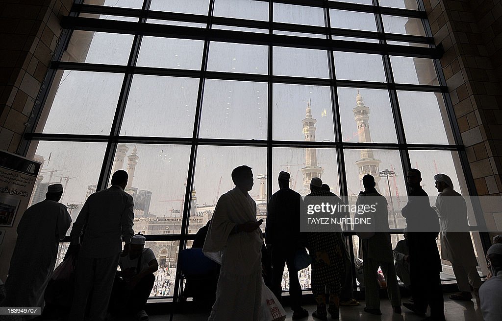 Muslim pilgrims look at Mecca's Grand Mosque from behind a window on October 10, 2013, as more than 2 million Muslims have arrived in Saudi Arabia for the hajj pilgrimage to the shrine city, the world's largest annual human assembly which peaks on October 13, according to local state media. AFP PHOTO/FAYEZ NURELDINE