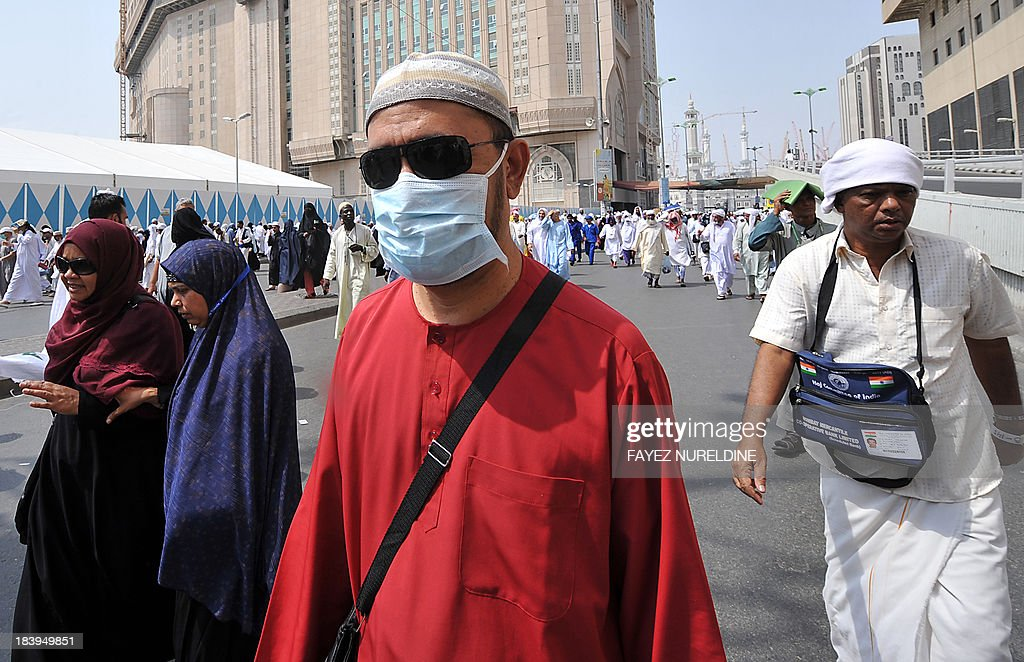 Muslim pilgrims, one of them wearing a mask, walk nearby Mecca's Grand Mosque on October 10, 2013, as more than 2 million Muslims have arrived in Saudi Arabia for the hajj pilgrimage to the shrine city, the world's largest annual human assembly which peaks on October 13, according to local state media. AFP PHOTO/FAYEZ NURELDINE
