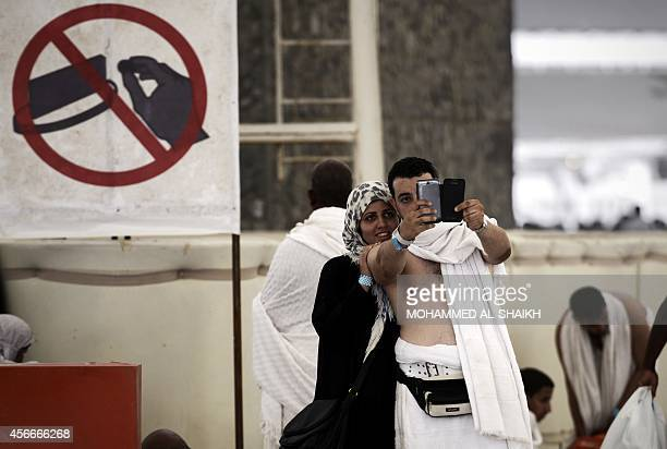 Muslim pilgrims pose for a selfie during the 'Jamarat' ritual the stoning of Satan in Mina near the holy city of Mecca on October 4 2014 Pilgrims...