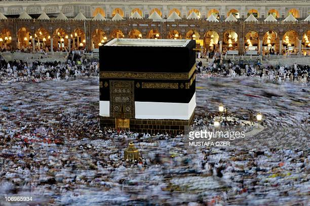 Muslim pilgrims reach to touch the golden doors of the Kaaba as they perform the walk around the Kaaba at the Grand Mosque in the Saudi holy city of...
