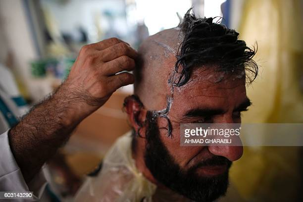 A Muslim pilgrims shaves his hair after throwing pebbles at pillars during the 'Jamarat' ritual the stoning of Satan in Mina near the holy city of...