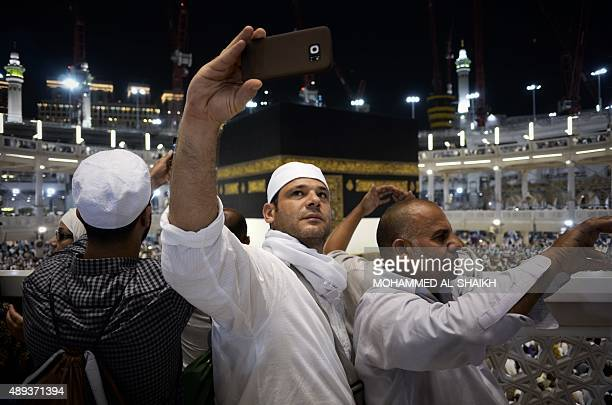 Muslim pilgrims take picture near the Islam's holiest shrine the Kaaba at the Grand Mosque in the Saudi holy city of Mecca late on September 20 2015...