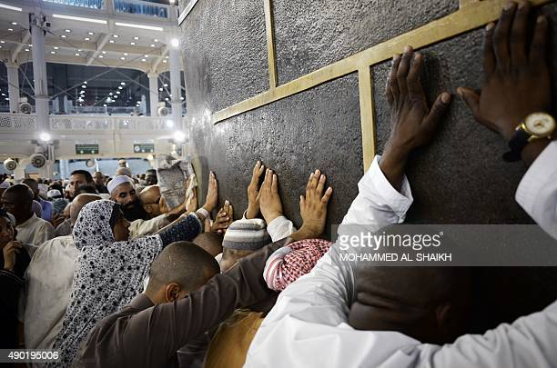 Muslim pilgrims touch Islam's holiest shrine the Kaaba at the Grand Mosque in Saudi Arabia's holy Muslim city of Mecca late on September 26 2015 At...