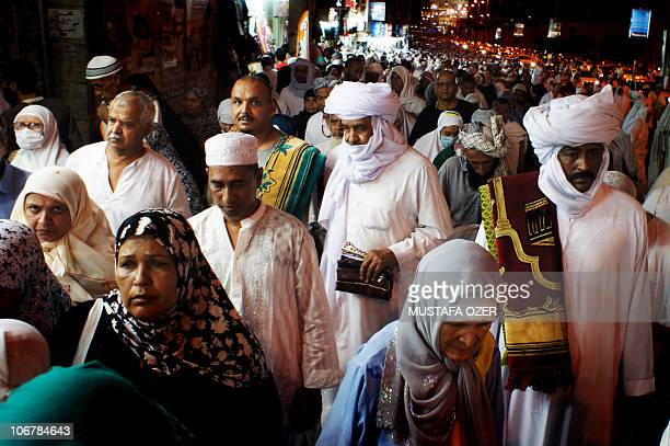 Muslim pilgrims walk in a main street following the evening prayer in the Saudi holy city of Mecca on November 12 2010 The annual pilgrimage or hajj...