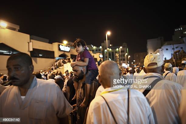Muslim pilgrims walk on the Al Arab market road where a deadly stampede took place in Mina near the holy city of Mecca late on September 25 2015 At...