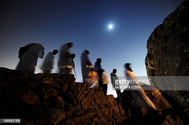 Muslim pilgrims walk on top of Noor mountain where the Hiraa cave is located overlooking Mecca late on November 13 as some 25 million Muslim pilgrims...