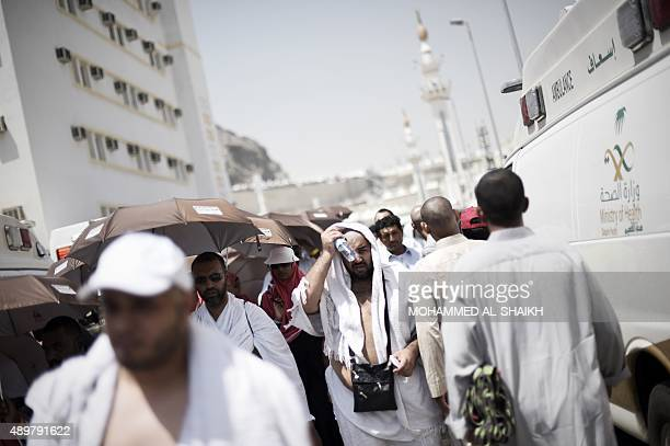 Muslim pilgrims walk past Saudi ambulances carrying injured pilgrims at an emergency hospital in Mina near the holy city of Mecca on the first day of...