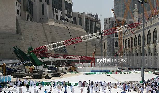Muslim pilgrims walk past the crane that collapsed the day before at the Grand Mosque in Saudi Arabia's holy Muslim city of Mecca on September 12...