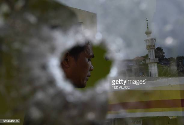 Muslim policeman prays inside a building riddled with bullet holes as a mosque is reflected on a glass window during a lull in fighting in Marawi on...