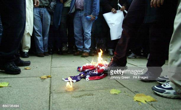 Muslim protesters burn an American flag at a demonstration against the USled bombings of Afghanistan outside the London Central Mosque by Regents...