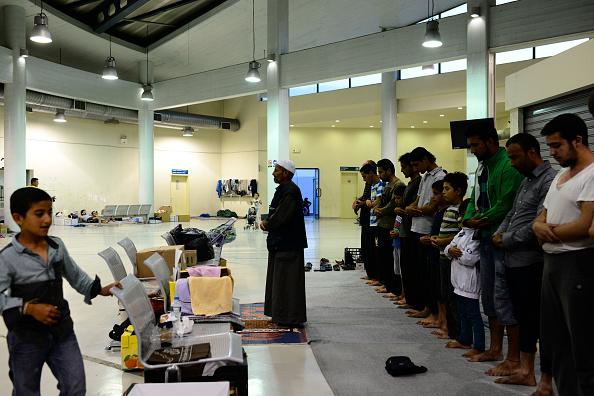 Muslim refugees pray at sundown in Piraeus port terminal...