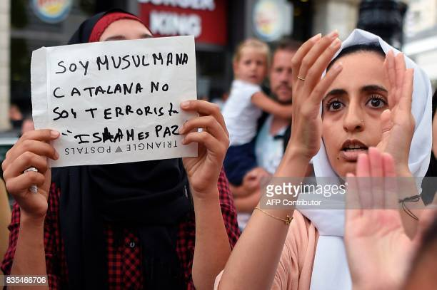 A Muslim resident of Barcelona holds a message reading 'I am a muslim Catalan i am not a terrorist Islam is peace' as they demonstrate on the Las...
