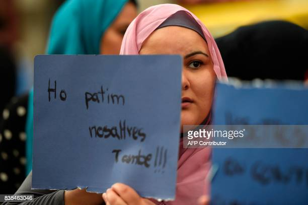 A Muslim resident of Barcelona holds a placard reading 'We are also afraid' as they demonstrate on the Las Ramblas boulevard in Barcelona to protest...