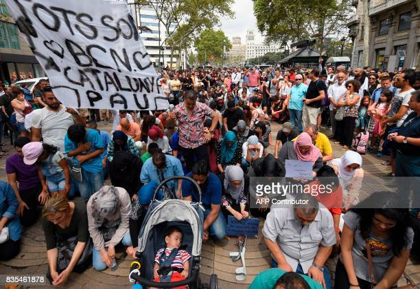 Muslim residents of Barcelona kneel on the Las Ramblas boulevard as they demonstrate in Barcelona to protest against terrorism and in tribute to the...