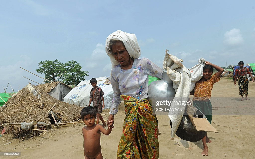 Muslim Rohingya carry their belongings as they arrive back to a camp for iternally displaced people in the village of Mansi on the outskirts of Sittwe on May 17, 2013. Bangladesh and Myanmar cleaned up on May 17 after a killer cyclone wrecked thousands of homes, relieved that the damage was not much worse after the storm weakened as it made landfall. At least 40 people were either killed by Cyclone Mahasen or while trying to flee its impact, including 25 Muslim Rohingya whose bodies washed up on the shores of Bangladesh after their boat capsized while sailing from Myanmar. AFP PHOTO / Soe Than WIN