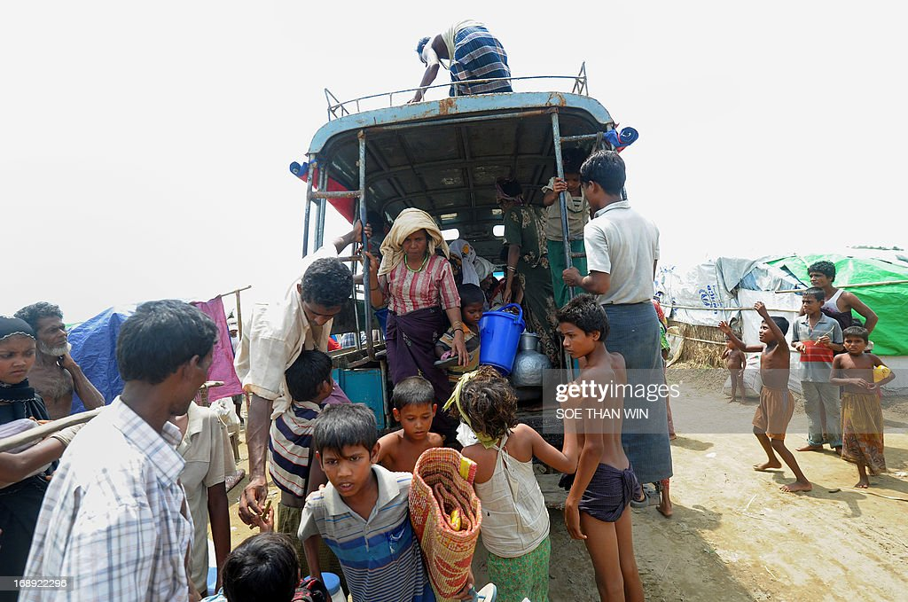 Muslim Rohingya families unload their belongings from a truck as they arrive back to a camp for iternally displaced people in the village of Mansi on the outskirts of Sittwe on May 17, 2013. Bangladesh and Myanmar cleaned up on May 17 after a killer cyclone wrecked thousands of homes, relieved that the damage was not much worse after the storm weakened as it made landfall. At least 40 people were either killed by Cyclone Mahasen or while trying to flee its impact, including 25 Muslim Rohingya whose bodies washed up on the shores of Bangladesh after their boat capsized while sailing from Myanmar. AFP PHOTO / Soe Than WIN