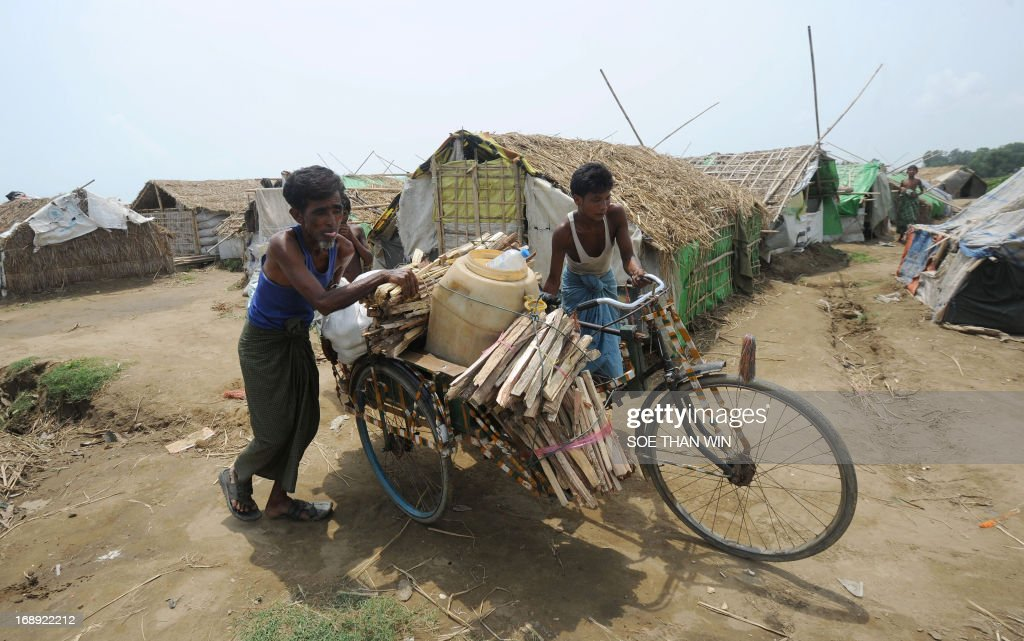 Muslim Rohingya men transport their belongings on a tricycle as they arrive back to a camp for iternally displaced people in the village of Mansi on the outskirts of Sittwe on May 17, 2013. Bangladesh and Myanmar cleaned up on May 17 after a killer cyclone wrecked thousands of homes, relieved that the damage was not much worse after the storm weakened as it made landfall. At least 40 people were either killed by Cyclone Mahasen or while trying to flee its impact, including 25 Muslim Rohingya whose bodies washed up on the shores of Bangladesh after their boat capsized while sailing from Myanmar. AFP PHOTO / Soe Than WIN