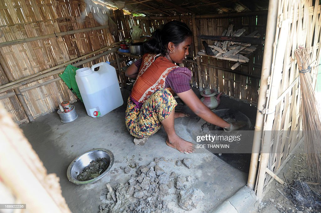 A Muslim Rohingya woman prepares her kitchen after arriving back to a camp for iternally displaced people in the village of Mansi on the outskirts of Sittwe on May 17, 2013. Bangladesh and Myanmar cleaned up on May 17 after a killer cyclone wrecked thousands of homes, relieved that the damage was not much worse after the storm weakened as it made landfall. At least 40 people were either killed by Cyclone Mahasen or while trying to flee its impact, including 25 Muslim Rohingya whose bodies washed up on the shores of Bangladesh after their boat capsized while sailing from Myanmar. AFP PHOTO / Soe Than WIN