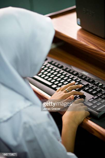 Muslim schoolgirl studying on a computer