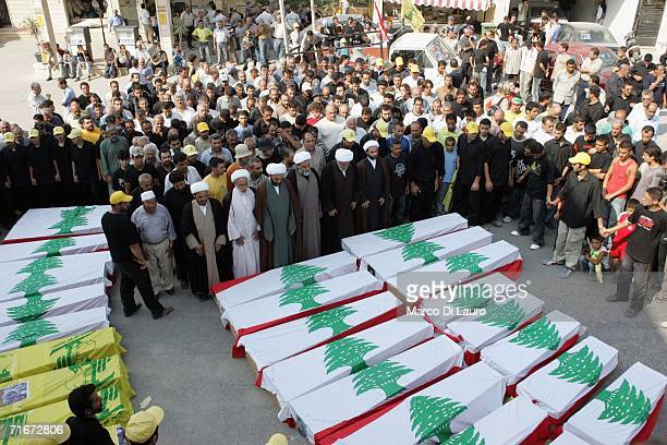 Muslim Sheik and relatives of the victims of the Qana air raid pray in front of the coffins during the funeral on August 18 2006 in Qana Southern...