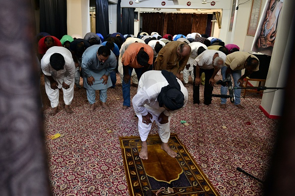 Muslim Shia migrants in Greece pray during the celebrations of Eid al-Fitr marking the end of the fasting month of Ramadan, at a makeshift mosque near the port of Piraeus on July 6, 2016
