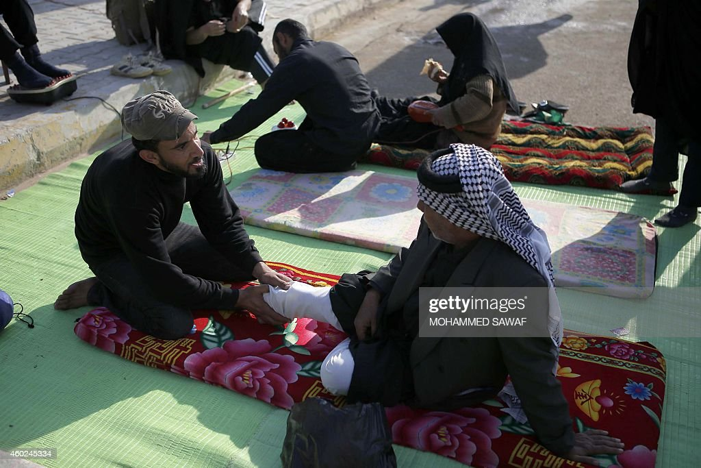 Muslim Shiite pilgrims rest their feet as they arrive in the shrine central city of Karbala on December 9 where they take part in the Arbaeen...