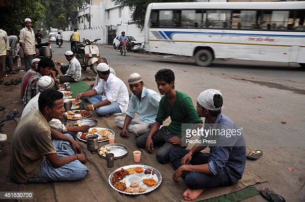 Muslim shopkeepers end their fasting period after sunset by having an evening meal on the roadside in Allahabad during the Islamic month of Ramadan