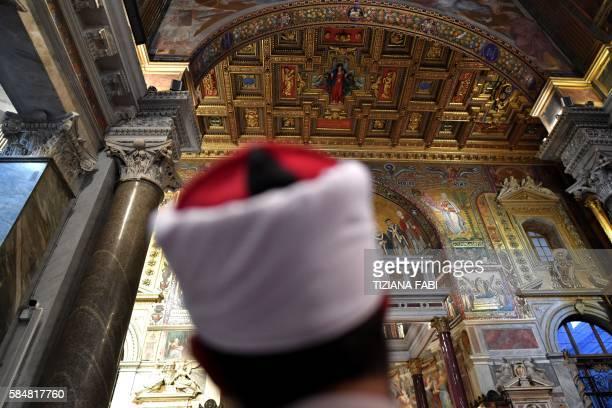 TOPSHOT A muslim take part in a mass in Santa Maria in trastevere church in Rome on 31 July 2016 Muslims participate in Catholic ceremonies in...