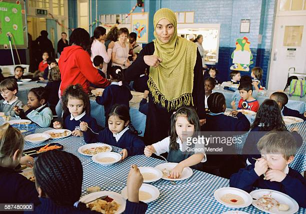 A Muslim teacher oversees Reception Year pupils as they eat their school dinner at Millfields Community School The school has worked hard to improve...